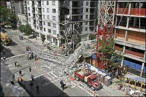 A large crane lies in the middle of a large New York City intersection.  The crane collapsed Friday May 30, 2008